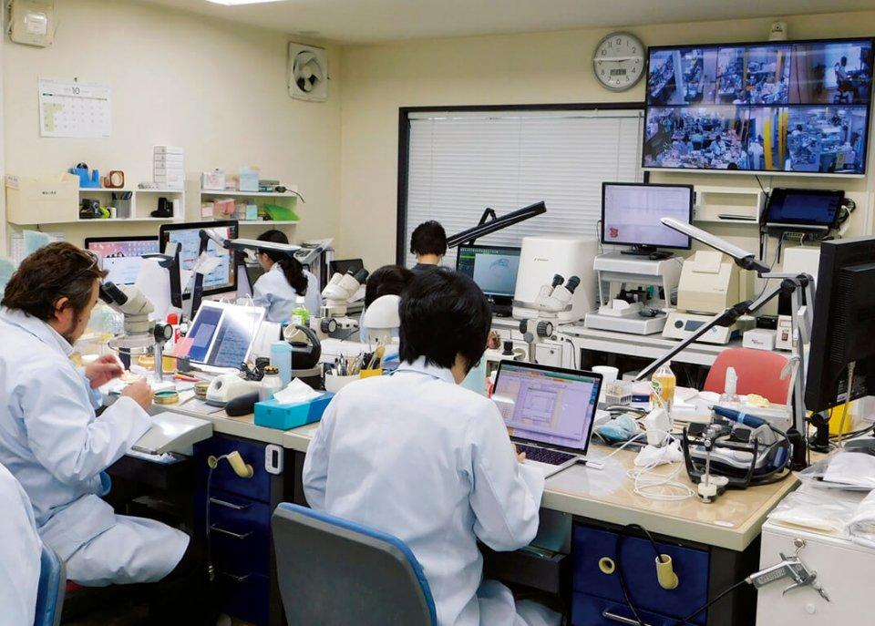 少人数の会社が多い業界の中で、協和デンタル・ラボラトリーでは多数の歯科技工士を雇用している。右上にあるモニターは沖縄在住の社員の勤務状況が映っている