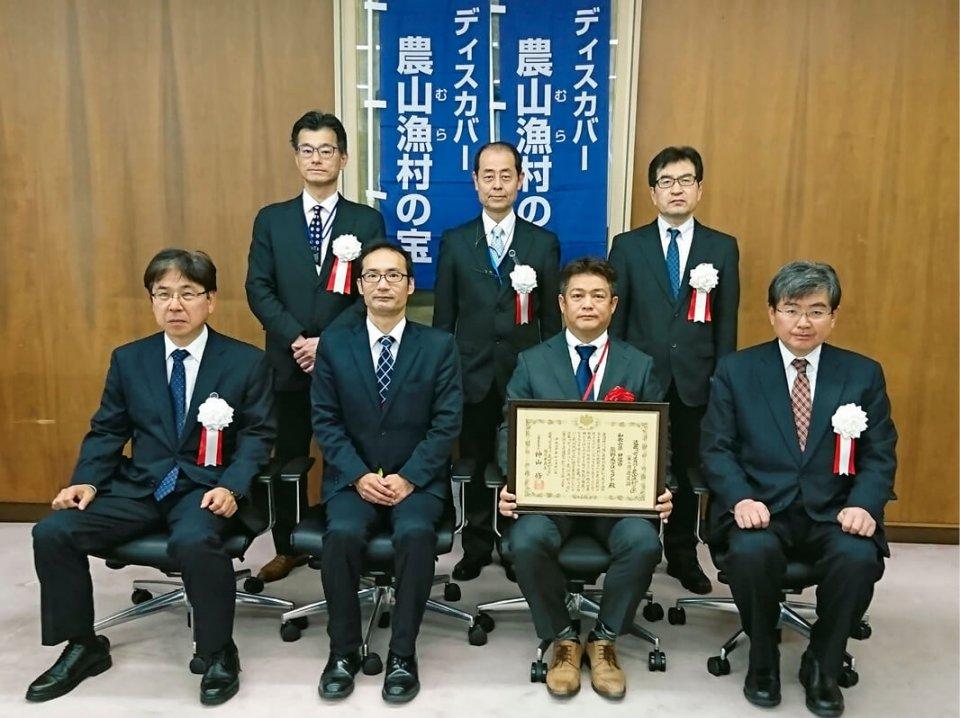 選定証授与式にはプロジェクト代表、たがみの田上雅人専務(前列中央右)と山田隆生指導員(同左)らが出席