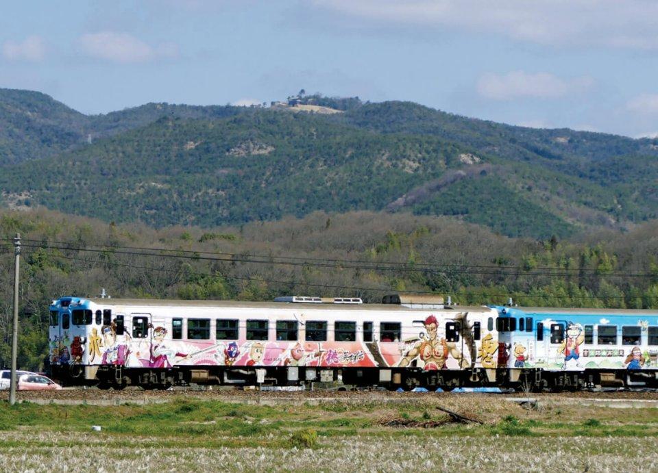 JR吉備線(桃太郎線)を走る昔話「桃太郎」と岡山の「温羅伝説」のラッピング列車。後方の鬼城山に「鬼ノ城」が見える