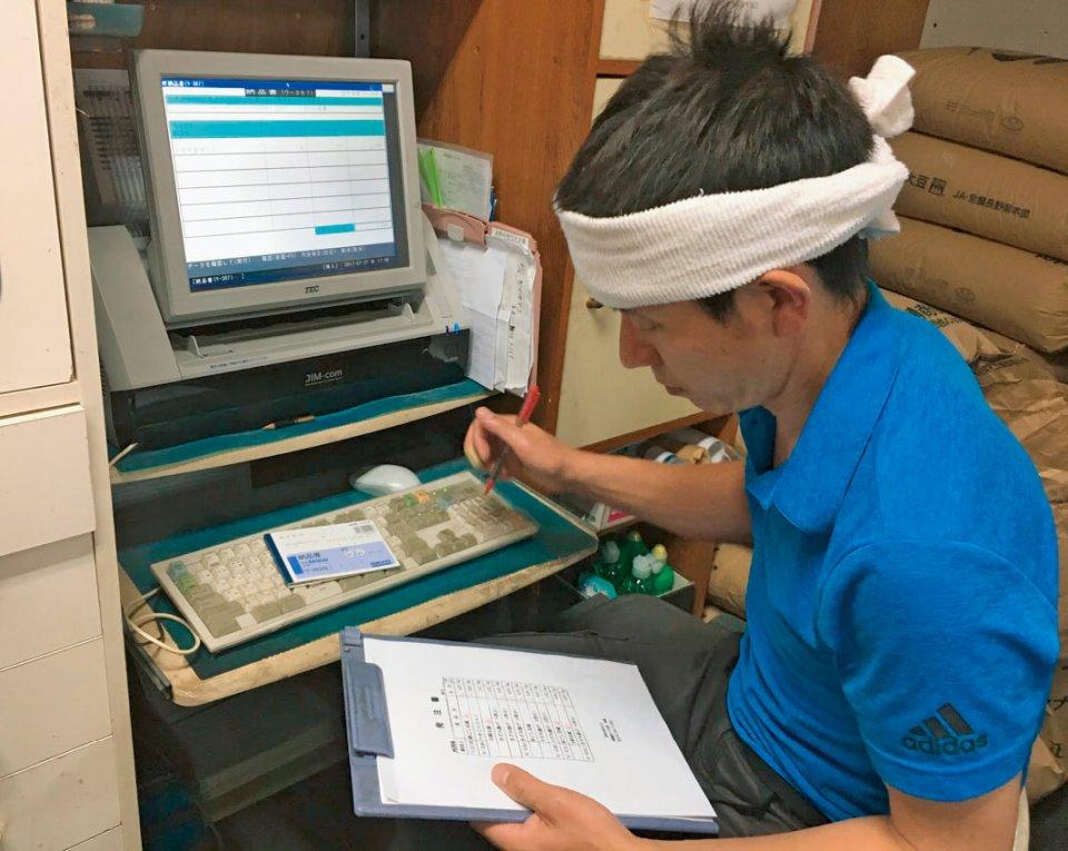 両国屋豆腐店の石垣さんは閉店後に入力作業をしていた