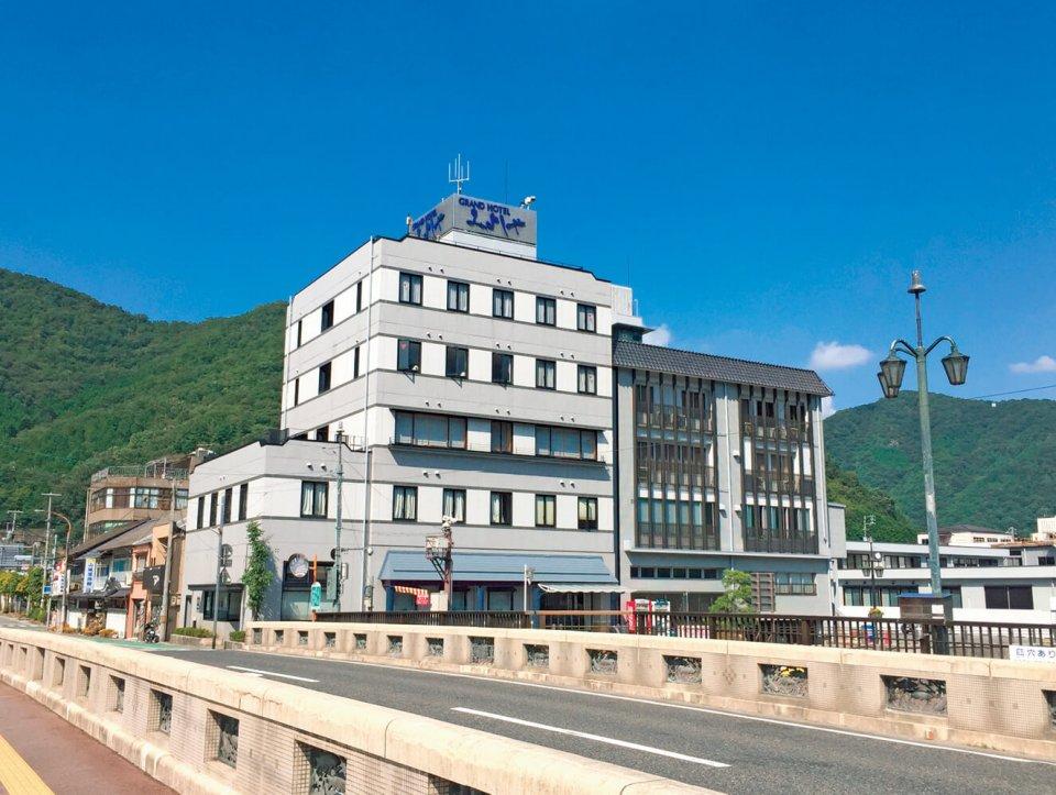 「グランドホテルみよしや」はJR伯備線新見駅から徒歩1分の好立地。高梁川に面して建つ