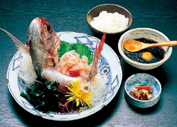 宇和島鯛めし:新鮮なタイの刺身をしょうゆ、みりん、卵、だし汁で調理されたタレに漬け込み、熱々のご飯にかけて食べる