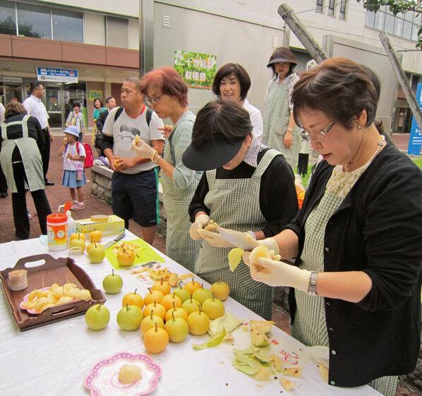 収穫した梨を振る舞うメンバーら(昨年)