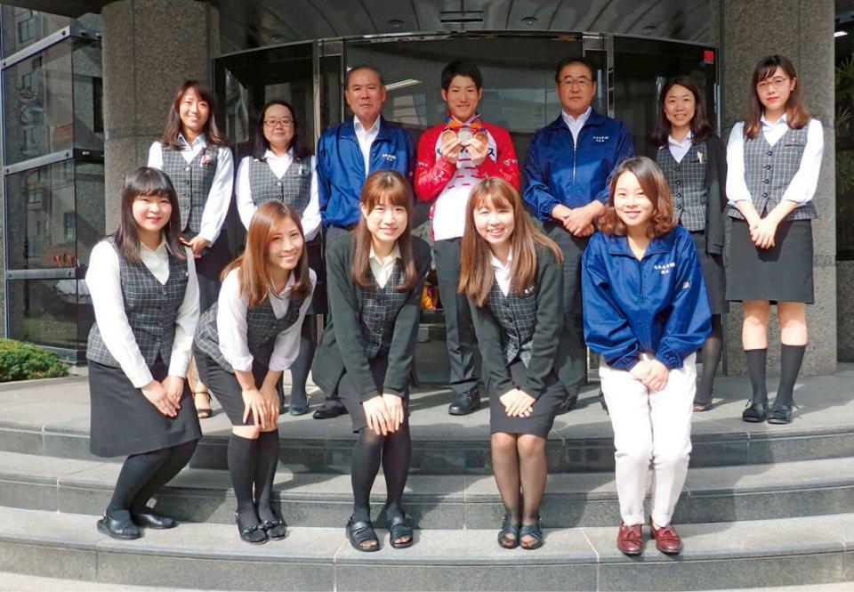 川本選手がアジアパラ競技大会2018で銀メダル1つ、銅メダル2つを獲得したことを報告に来た際、社員と一緒に記念撮影
