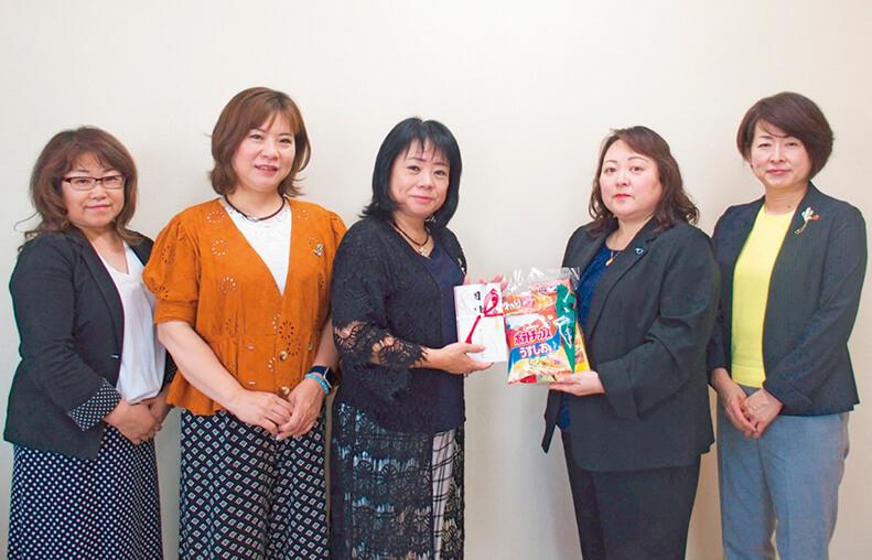 同所を訪れた白ゆり会の大野副会長(右から2人目)へ目録を贈呈する女性会の針尾会長(中央)
