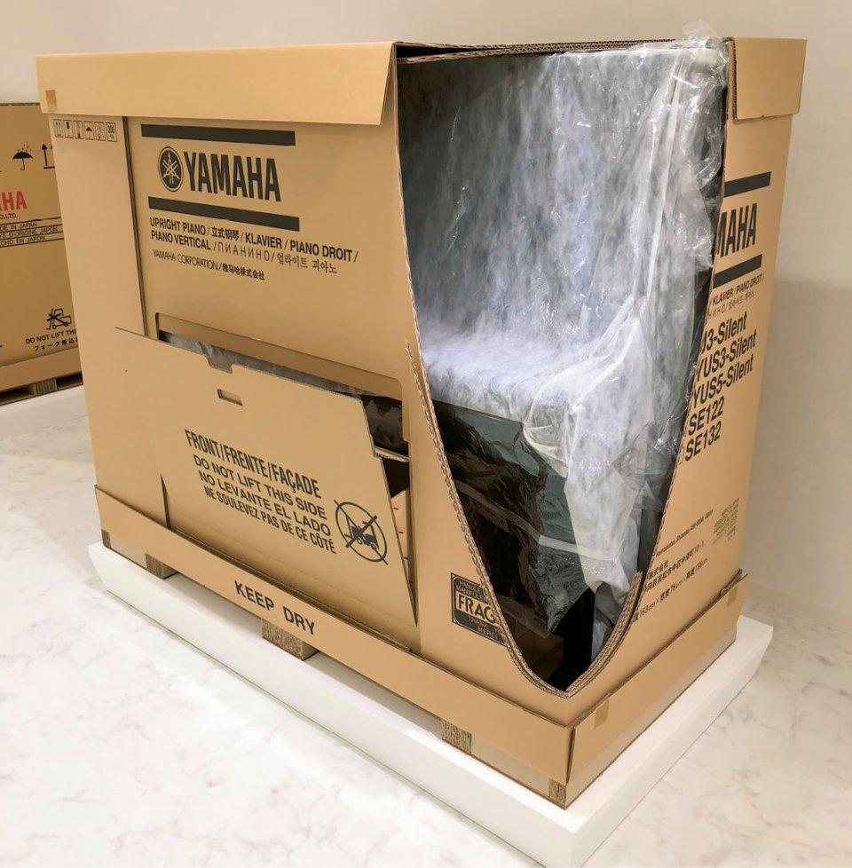 アップライトピアノ輸送用製品包装。中央下部の空間には、ピアノの椅子が同梱できるように工夫されている
