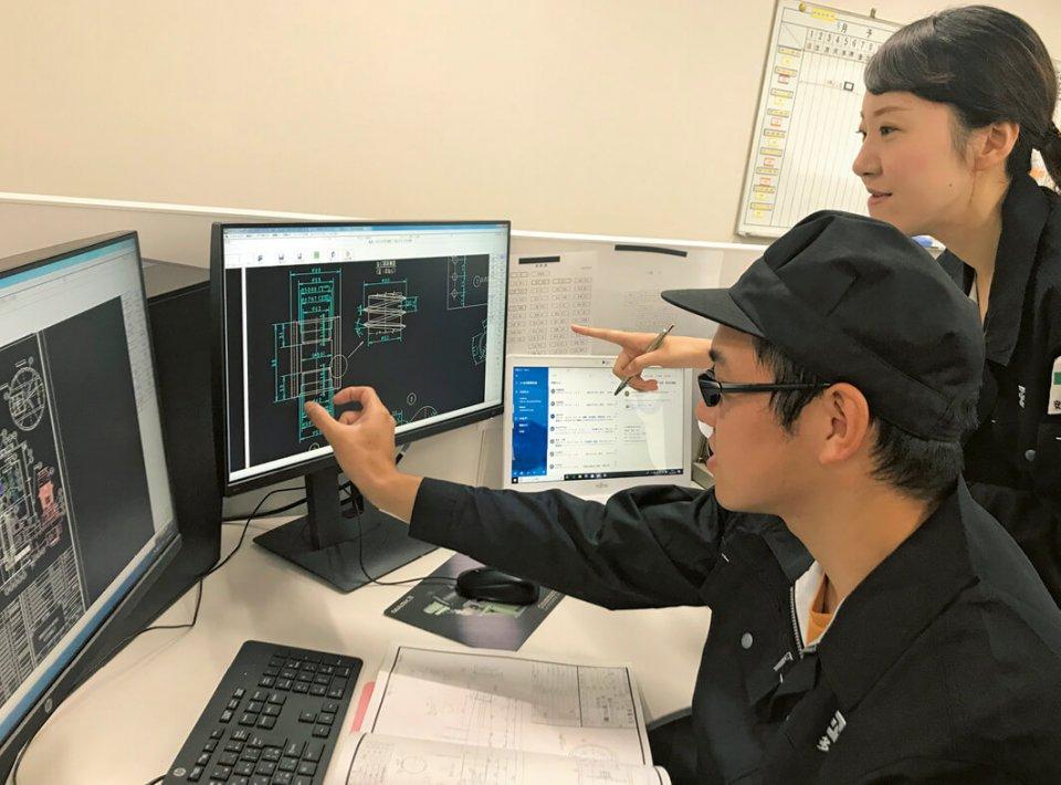 機械の図面を確認する技術部社員