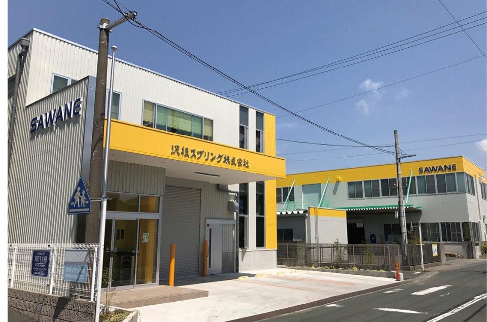 黄色のコーポレートカラーが映える、沢根スプリングの本社工場