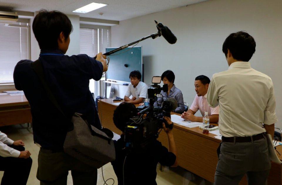 面接官を務めるYEGメンバーに取材する地元メディア