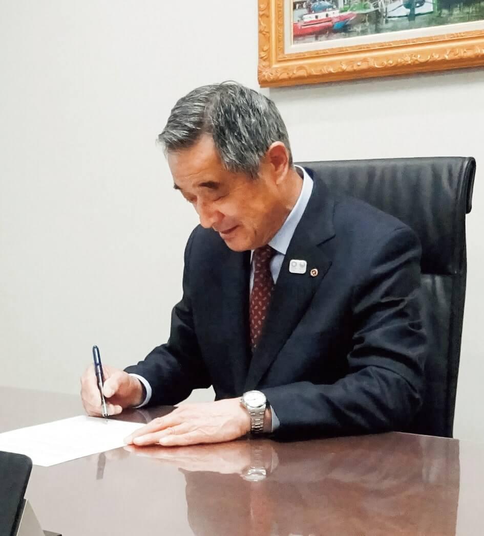 協定書に署名する増田会頭