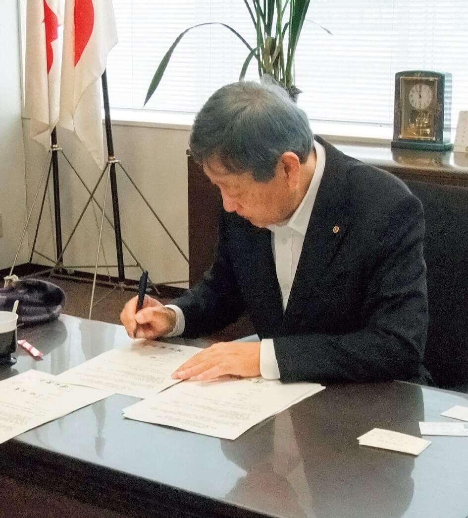 協定書に署名する小野会頭