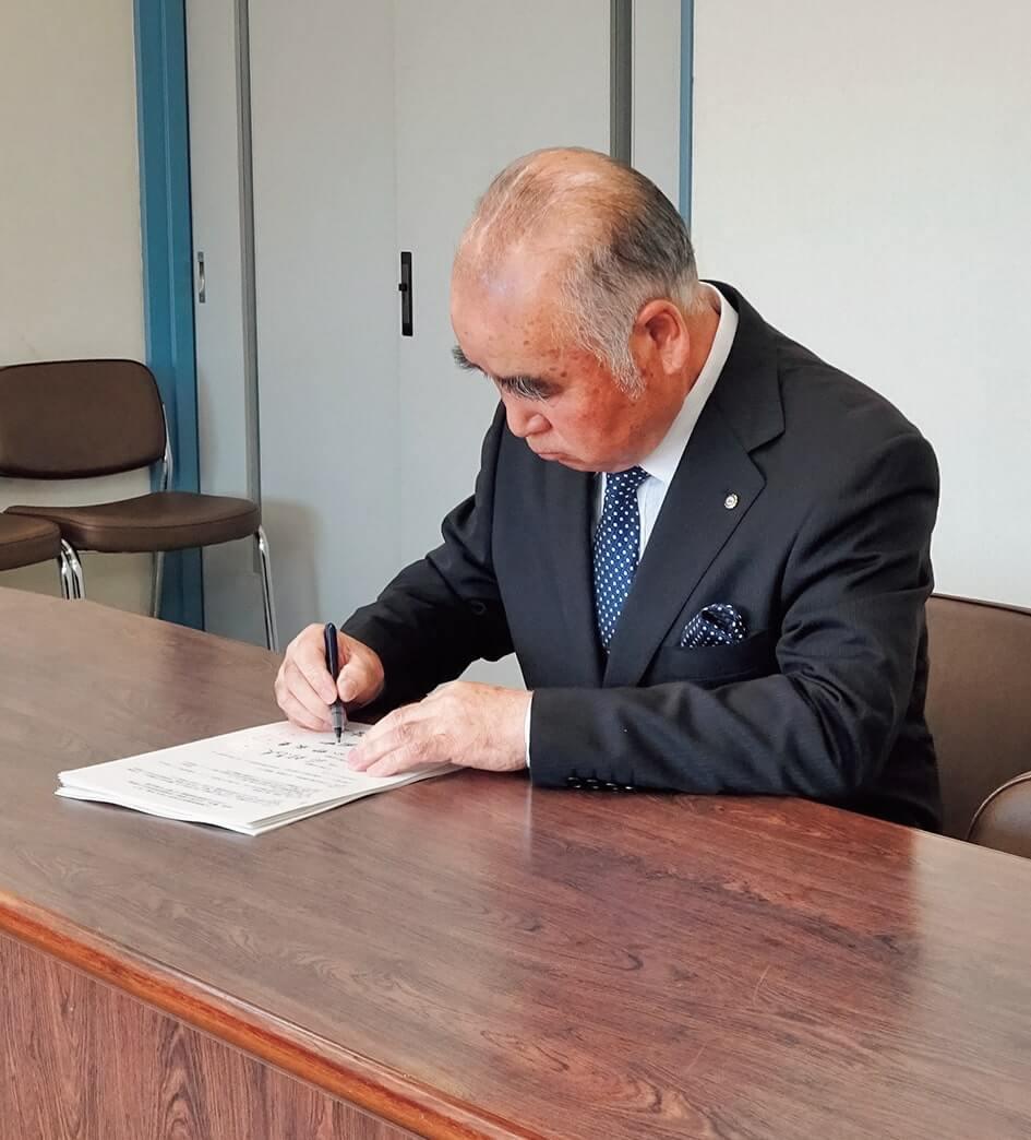 協定書に署名する平形会長