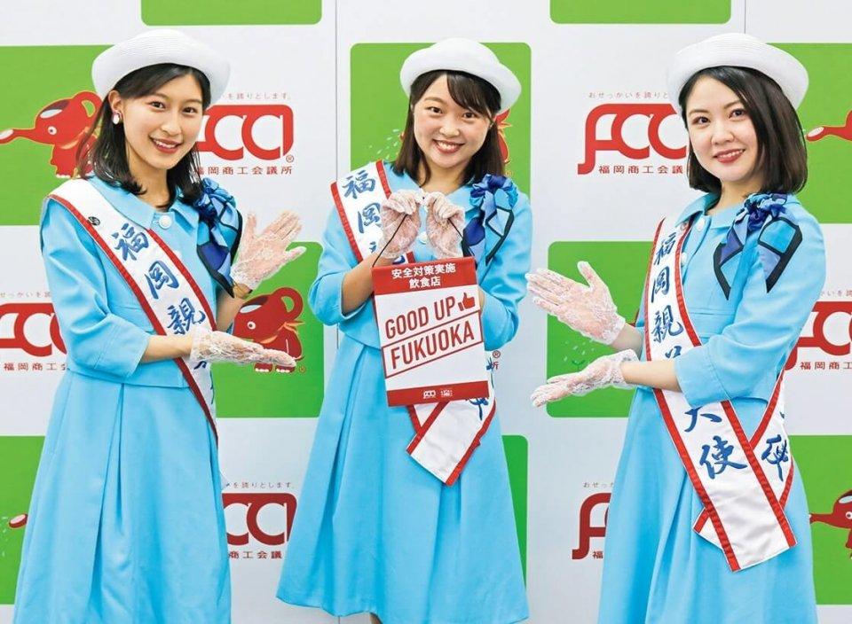 事業サポーターの福岡親善大使3人が参加店のタペストリーを紹介