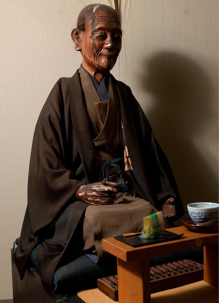 江戸時代の作という初代・伝蔵の木像。朝晩欠かさず茶と菓子を供えている