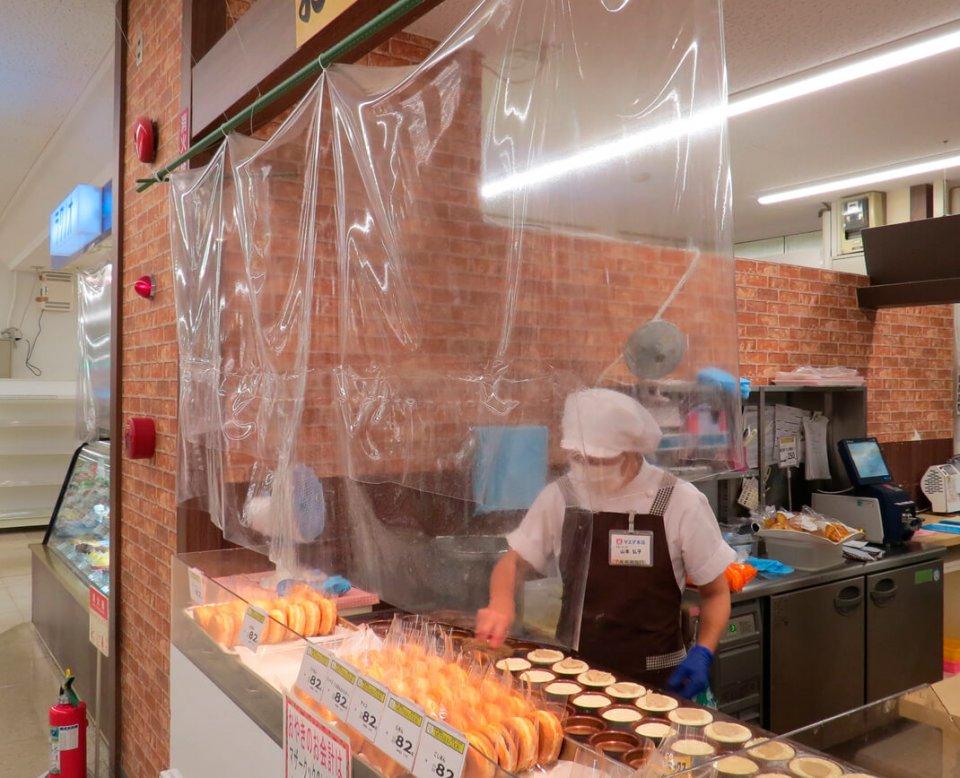 飛沫防止パーテーションで仕切られた大判焼き売り場。できたてのおいしさをそのままに、ビニール手袋や商品の個別包装などで安全面に配慮