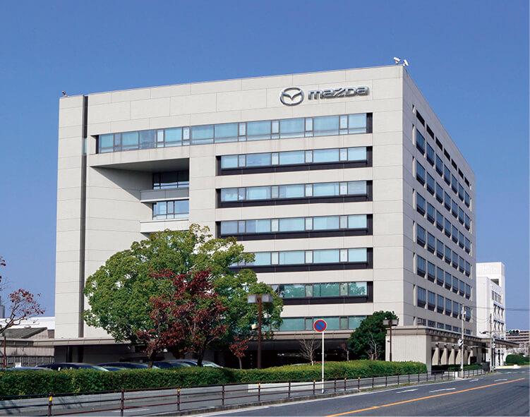 マツダの広島本社、広大な敷地内の一角に建つ。行き交う車、駐車場に止まる自動車のほとんどがマツダ社製だ