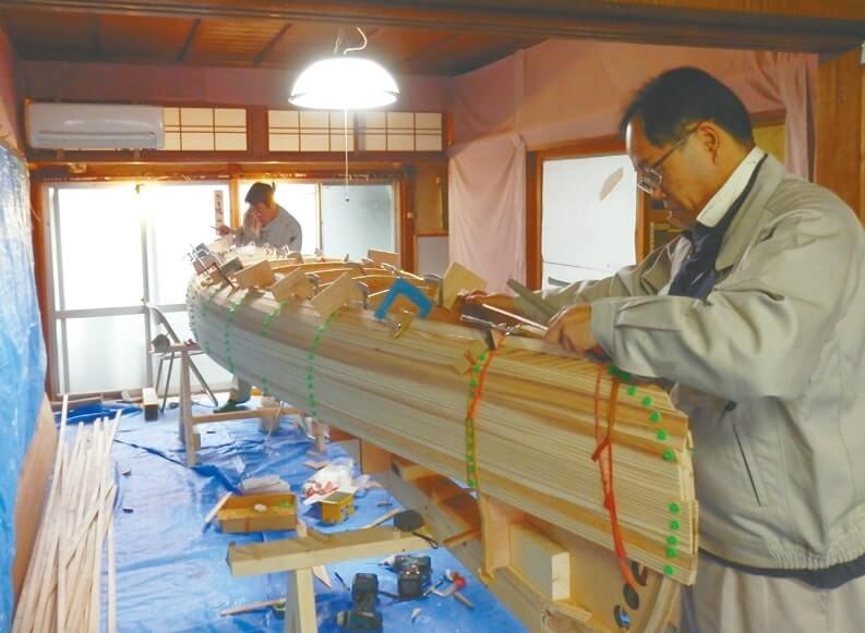 専門家の指導を受けながらカヌーを試作する職員
