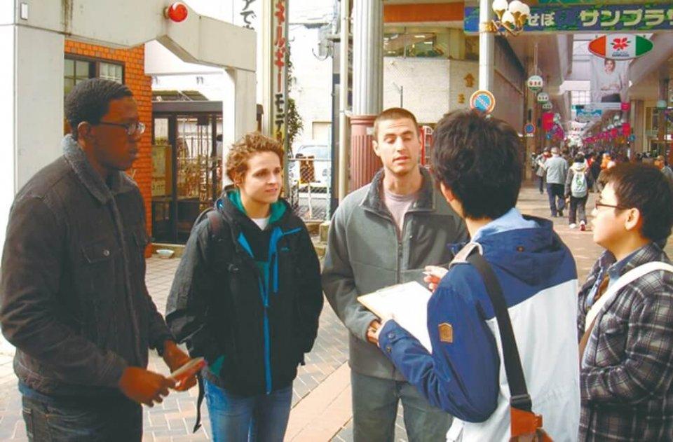学生グループが外国人に英文マップを配布。まちなかで困ることはないかなど、聞き取りも行った