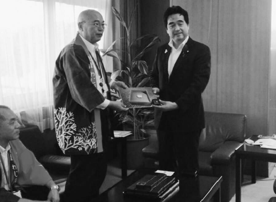 坂井国土交通省政務官(右)にVJCロゴバッジを手渡す梶輪島市長(左)