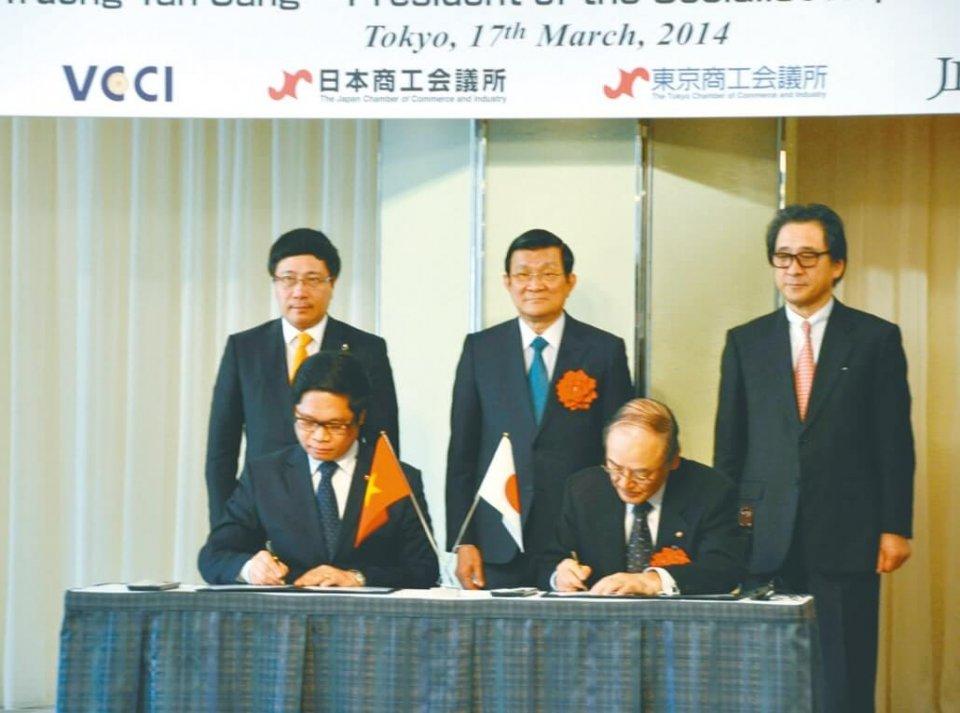 サン国家主席(後列中央)立会いのもと署名をする三村会頭(前列右)