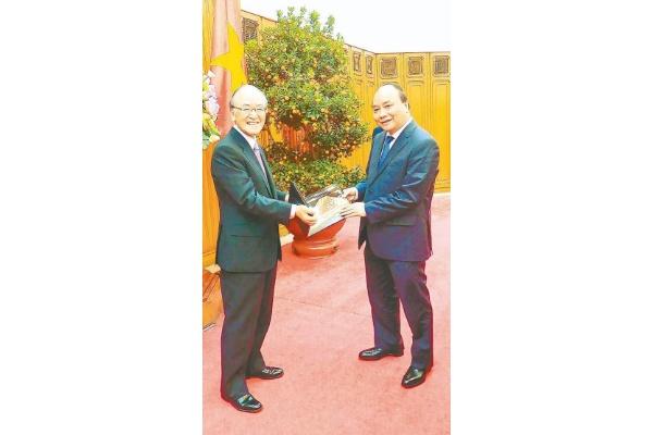 記念品交換する三村団長(左)とフック首相
