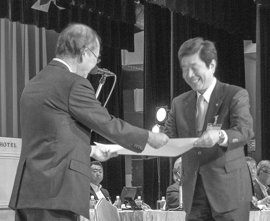 事業活動表彰を受ける上田・栁澤憲一郎
