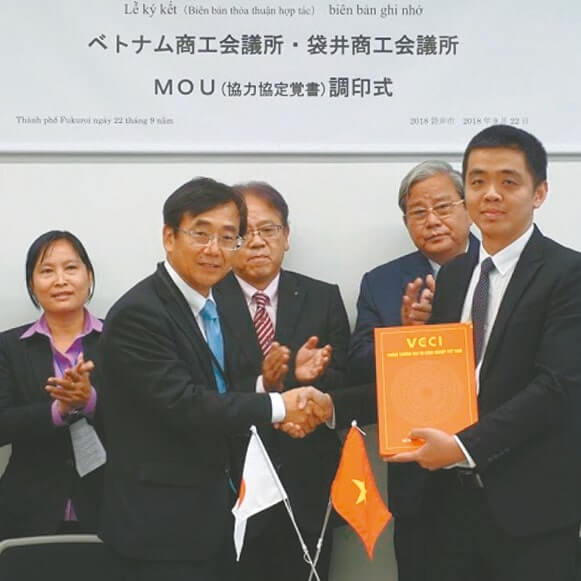 MOU調印式で訪問団のティェン代表と握手する水谷会頭(左)