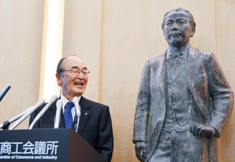 渋沢栄一像の横で記者団の取材に笑顔で応じる三村会頭