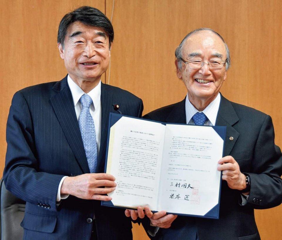 協定書に署名した三村会頭(右)と根本大臣