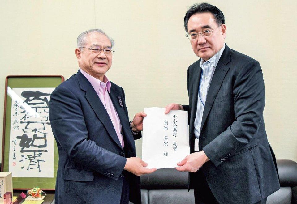 意見書を手交する西村委員長(左)と前田長官